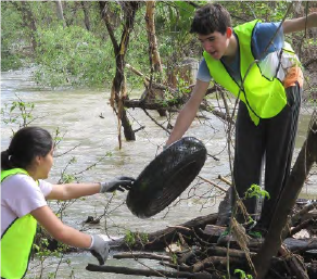 Person Picking up Tire at Creek Cleanup